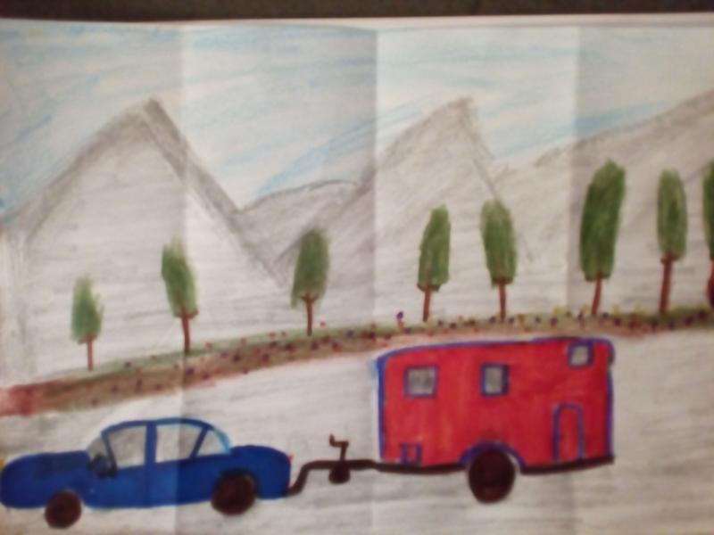 Auto mit Wohnwagen und Berge im Hintergrund.